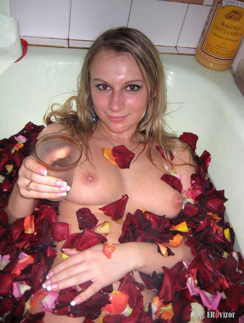 голая блондинка в ванной с лепестками из роз