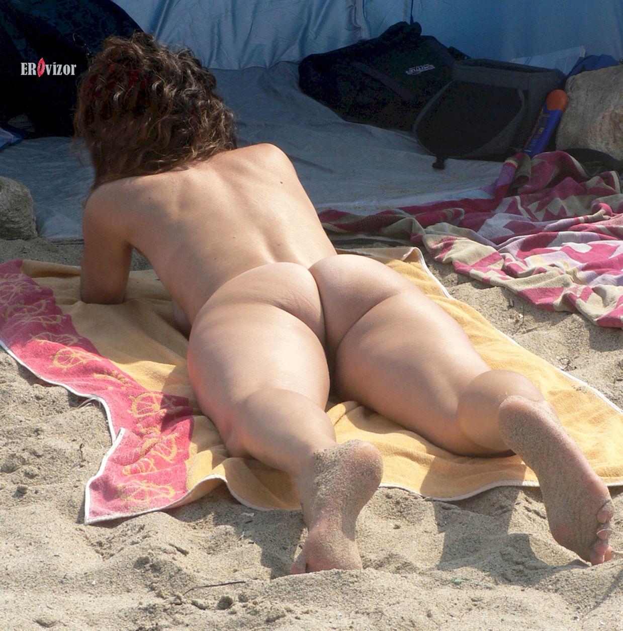 голая женщина лежит на пляже