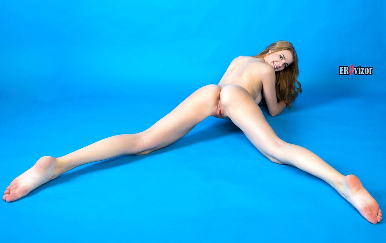 Голубоглазая девушка с длинными ногами раздвигает ягодицы