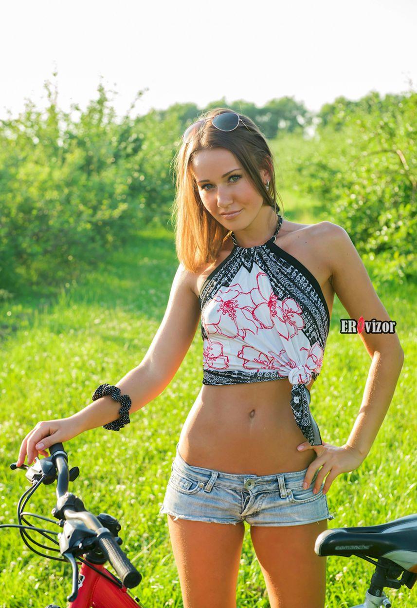 Стройная девушка с велосипедом раздевается на лоне природы