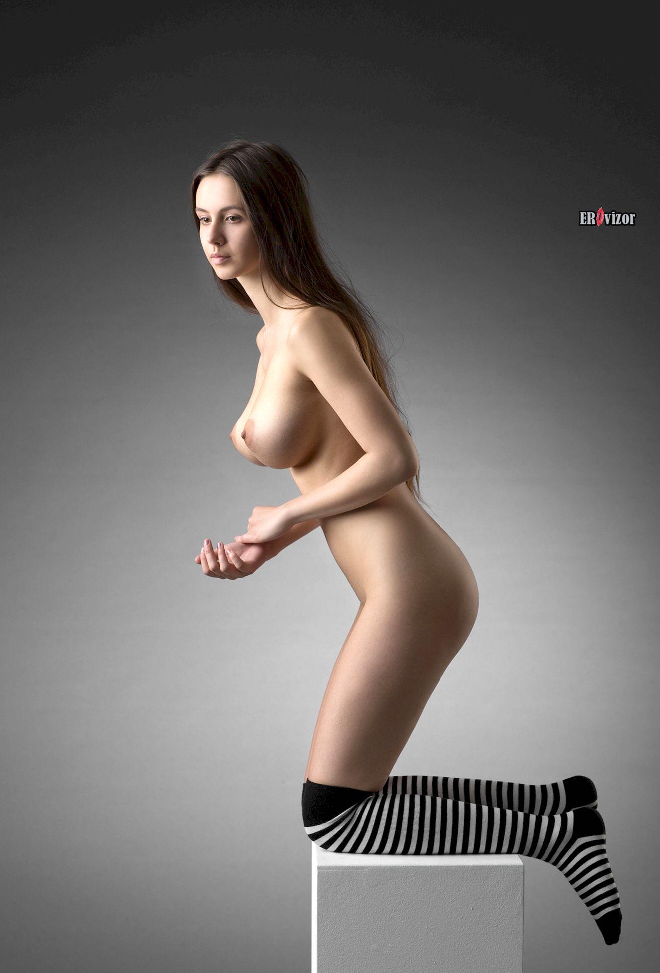 Голая няшка с большими сиськами эротично позирует в студии