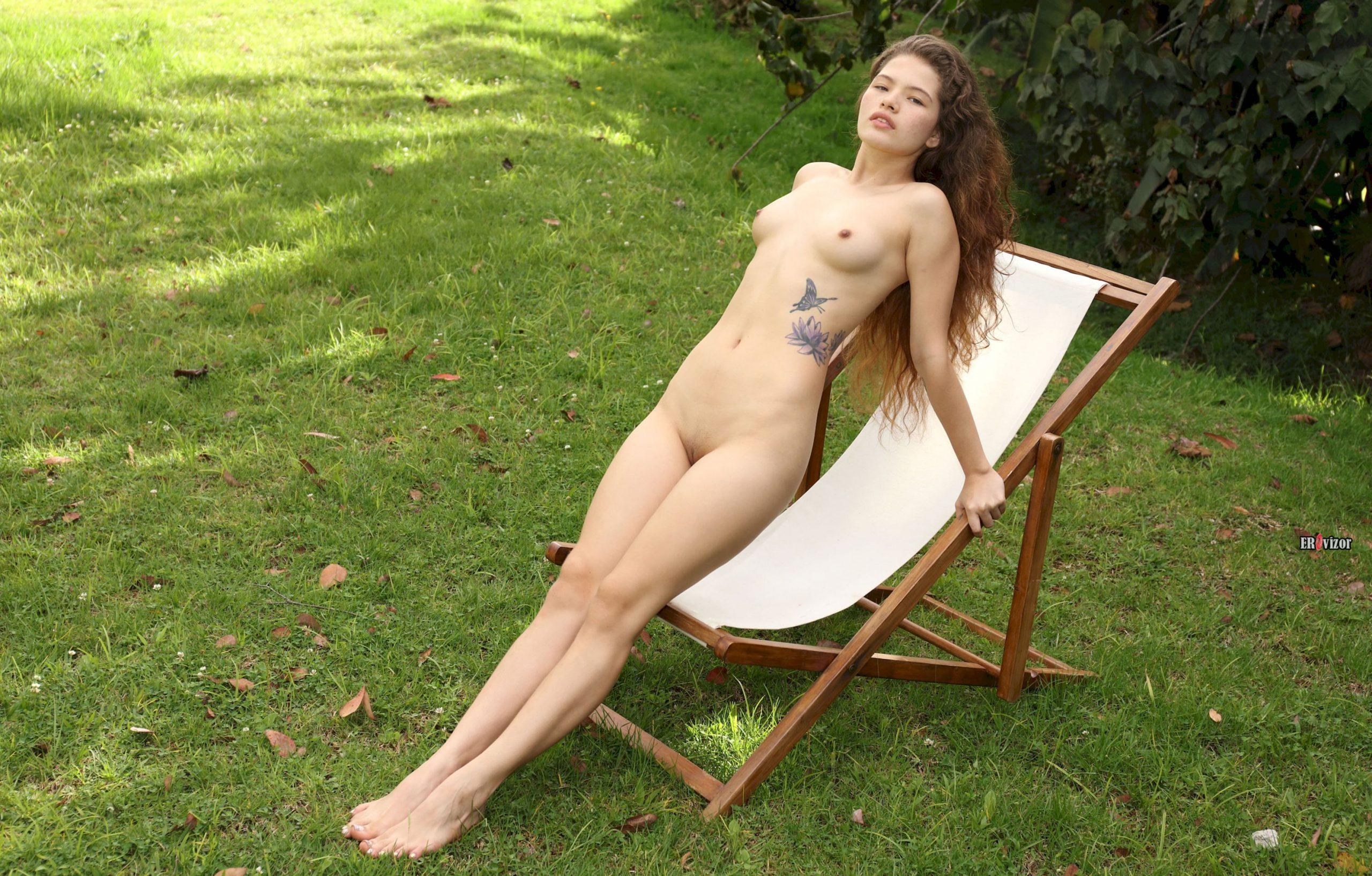 Молоденькая голая милашка на зеленой лужайке в шезлонге