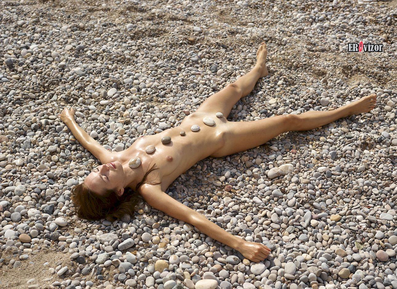 голая стройная девушки лежит на берегу