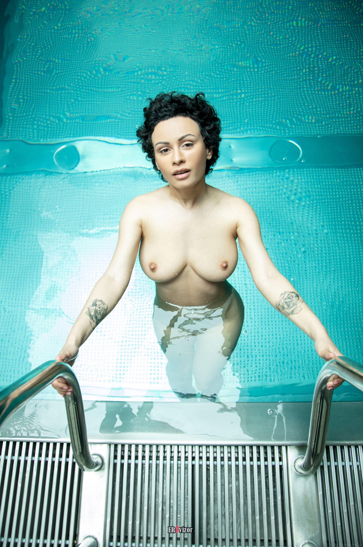 красивая девушка с кудрявыми волосами окунается в бассейн
