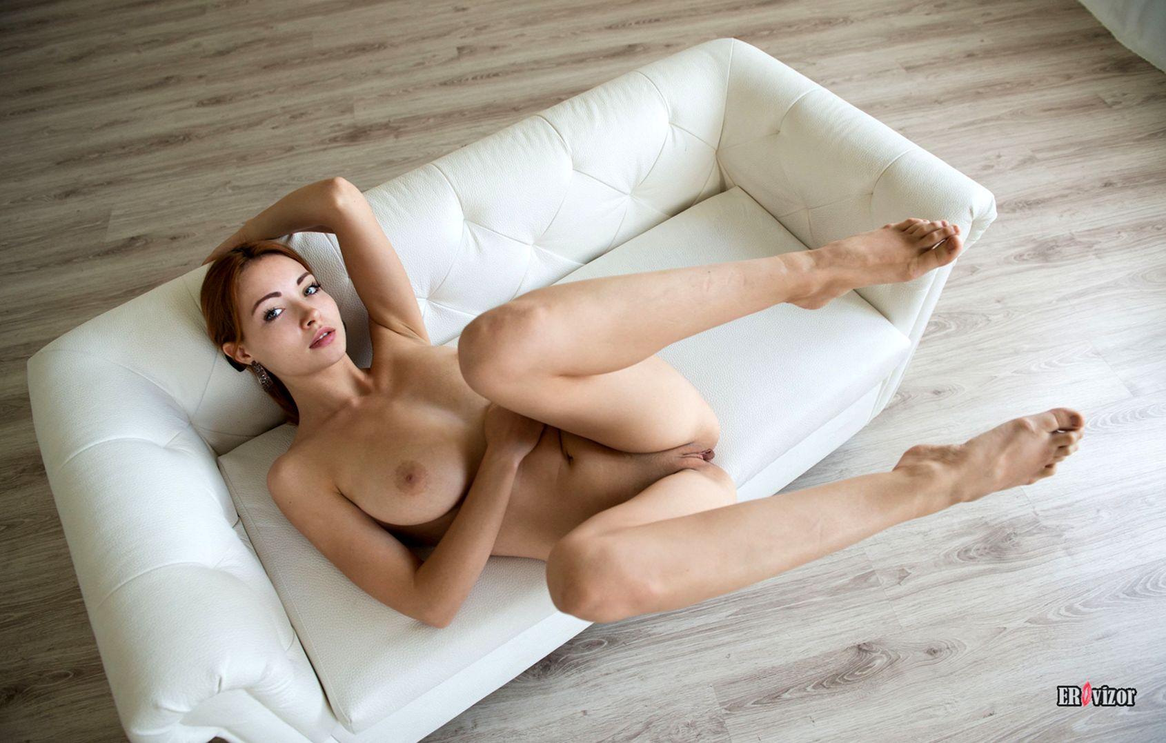 голая рыженькая модель лежа на белом диване